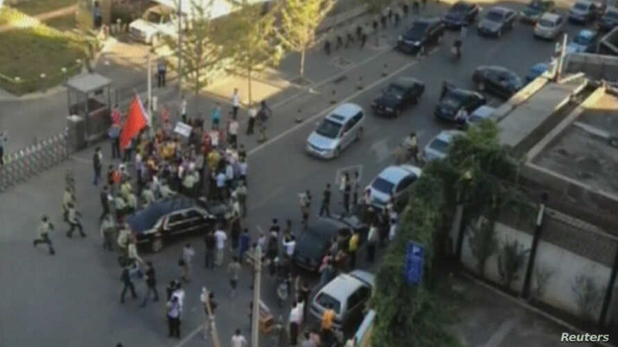 Security officers surround a car carrying U.S. ambassador Gary Locke after anti-Japan demonstrators tried to block the car outside the U.S. embassy in Beijing in this September 18, 2012 still image taken from video shot by Chinese dissidentAiWeiwei