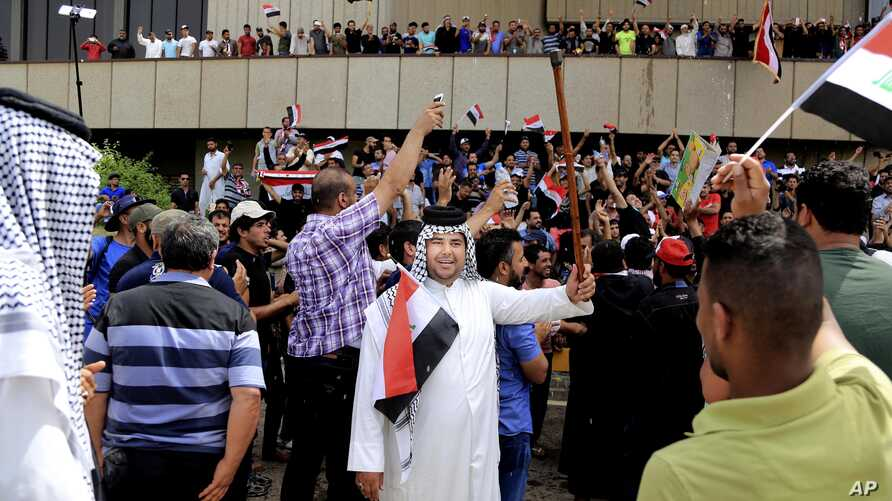 Supporters of Shi'ite cleric Muqtada al-Sadr chant slogans calling for governmental reforms as they wave national flags before ending their sit-in inside Baghdad's highly fortified Green Zone, May 1, 2016.