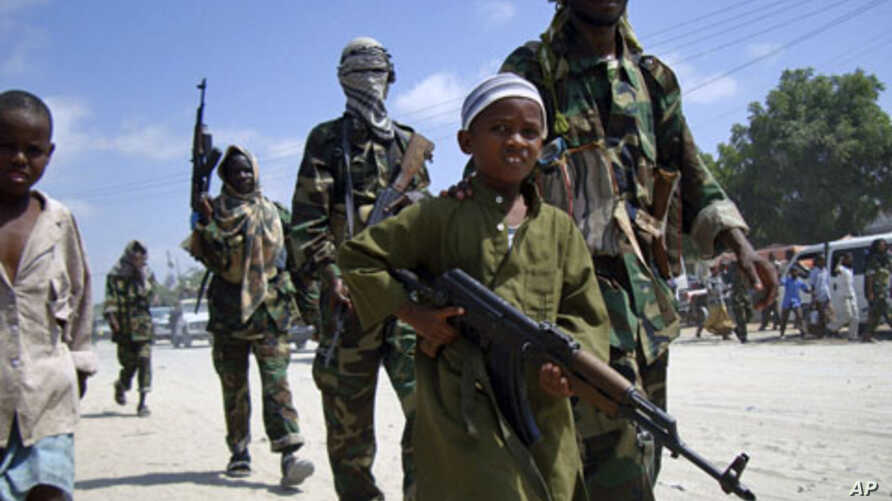 A young boy leads the hard-line Islamist Al Shabab fighters as they conduct military exercise in northern Mogadishu's Suqaholaha neighborhood, Somalia.  (File)