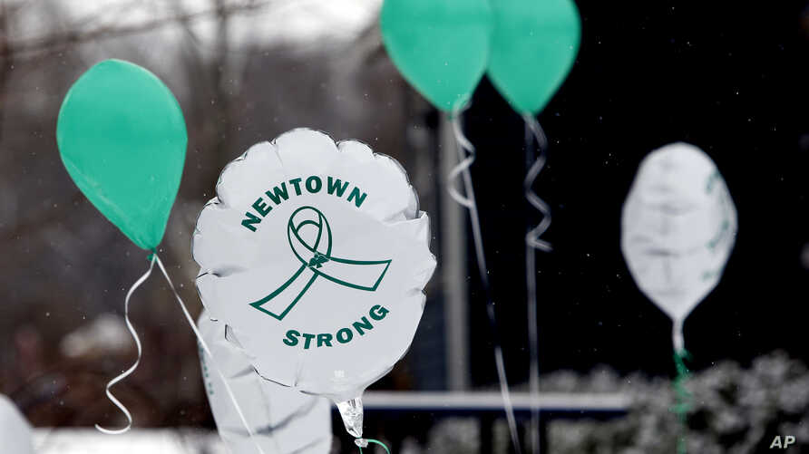 Balloons fly outside a doctor's office on the first anniversary of the Sandy Hook massacre, in Newtown, Conn., Saturday, Dec. 14, 2013. Bells tolled 26 times to honor the children and educators killed one year ago in a shooting rampage at Sandy Hook