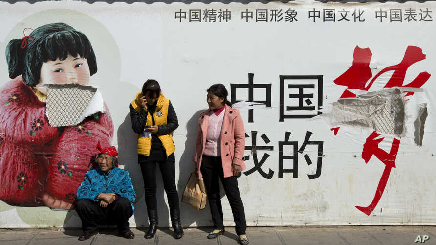 """Passengers wait in front of a broken propaganda poster featuring """"the China Dream"""" outside the Kunming Railway Station in Kunming, in western China's Yunnan province, Sunday, March 2, 2014."""