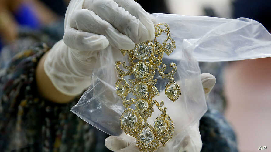 FILE - In this Nov. 24, 2015, file photo, a Bureau of Customs appraiser shows to the media a set of jewelry from Roumeliotes Collection, one of three sets of the Marcos Jewelry Collection, during appraisal at the Central Bank of the Philippines, in M