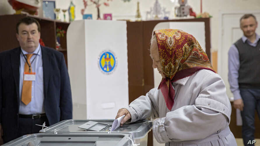 An elderly woman casts her vote at a polling station during presidential elections in Chisinau, Moldova, Oct. 30, 2016.