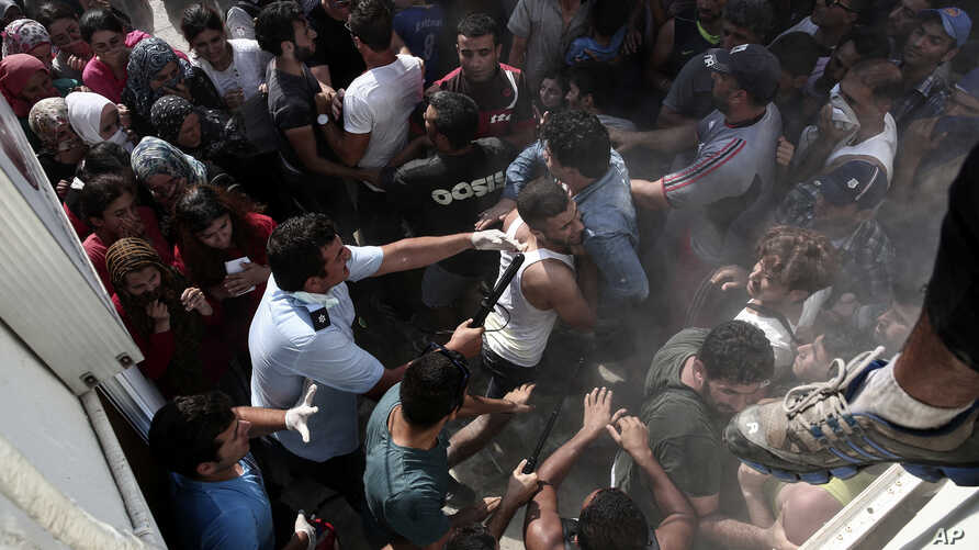 A policeman hits a migrant as police try to disperse hundreds of migrants during a registration procedure that was taking place at the stadium of Kos town, on the southeastern island of Kos, Greece, Aug. 11, 2015.