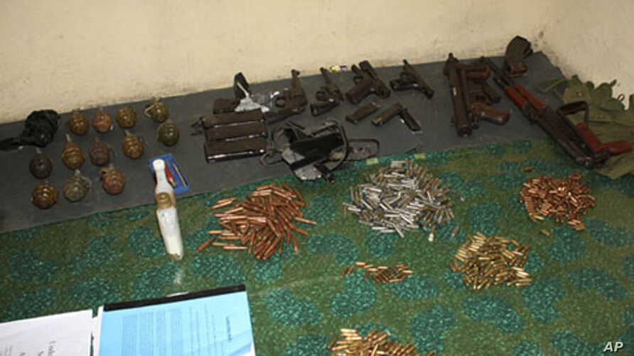 A cache of hand grenades and guns are displayed in Kayole, a low-income suburb about 15 km (10 miles) from Kenya's capital Nairobi, October 25, 2011.