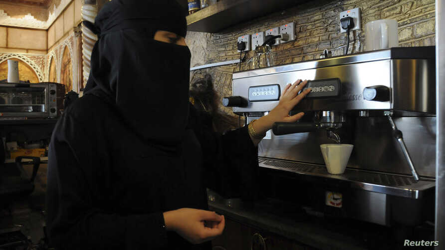 FILE - A veiled woman makes coffee as she works at a coffee shop in Tabuk, Saudi Arabia.