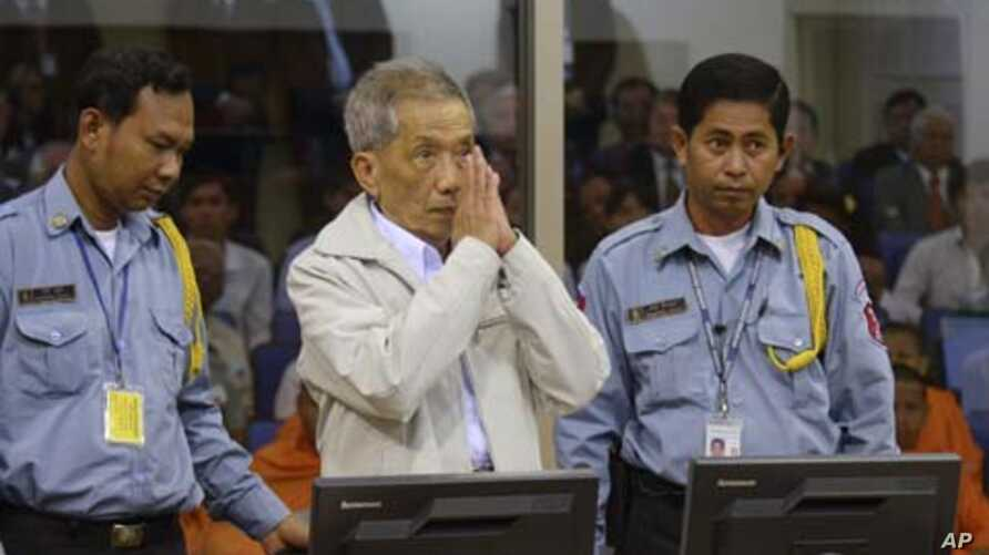Former Khmer Rouge S-21 prison chief Kaing Guek Eav alias Duch (C) greets the court during his appeal hearing at the Court Room of the Extraordinary Chambers in the Courts of Cambodia (ECCC) on the outskirts of Phnom Penh February 3, 2012. The United