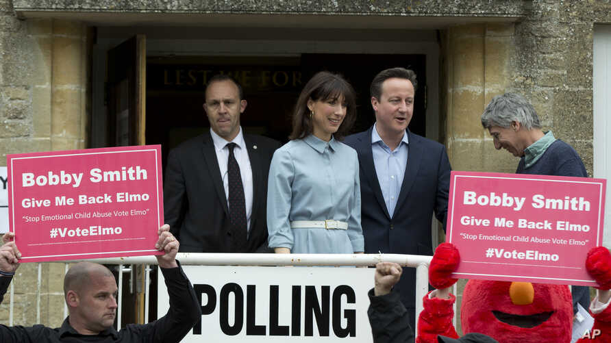 Britain's Prime Minister and Conservative Party leader David Cameron and his wife Samantha leave a voting station in Spelsbury, England, as protesters demonstrate outside after they voted in the general election, May 7, 2015.