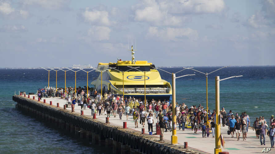 Tourists and passengers disembark from a ferry at Playa del Carmen, Mexico, March 2, 2018. Undetonated explosives were found on another ferry that runs between the Caribbean resorts of Playa del Carmen and the island of Cozumel, authorities said, les