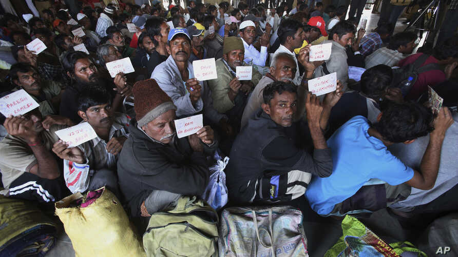 Released Indian fishermen display their name tags while waiting for train at a railway station to leave for their homeland India, in Karachi, Pakistan, Dec. 28, 2017.