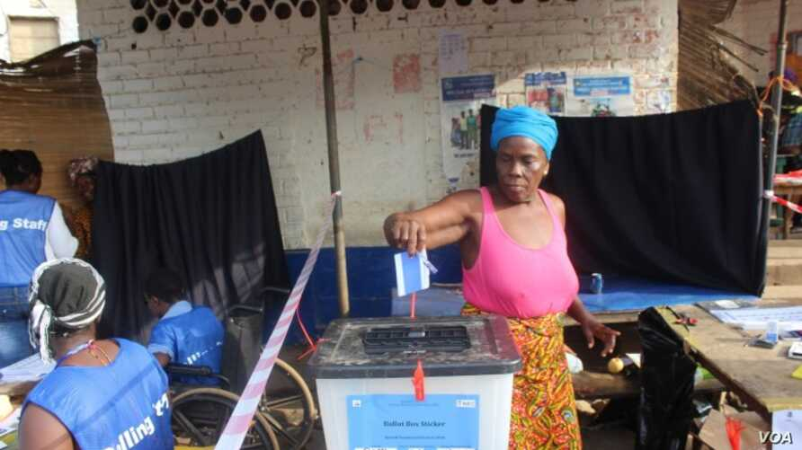 A woman votes in Liberia's Special Senatorial election