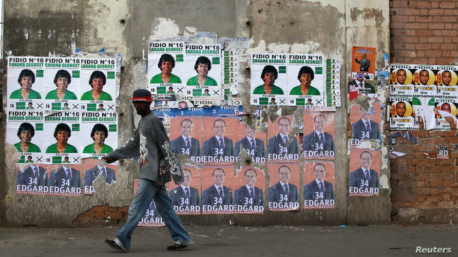 A man walks past campaign posters outside a polling center in Antananarivo, Madagascar, Oct. 25, 2013.