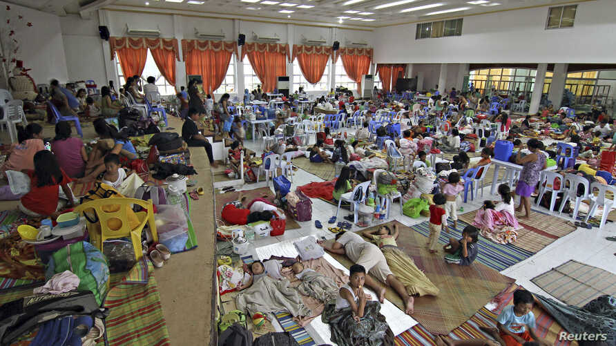 People take shelter inside a evacuation centre after evacuating from their homes due to super-typhoon Hagupit in Surigao city, southern Philippines, Dec. 5, 2014.