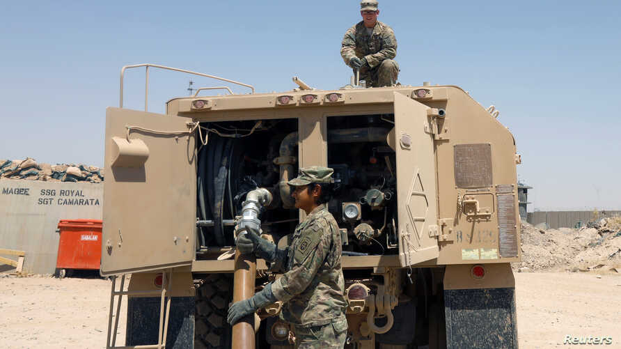 US army soldiers fuel a military truck at Qayyara airbase west of Mosul, Iraq, Aug. 10, 2017.