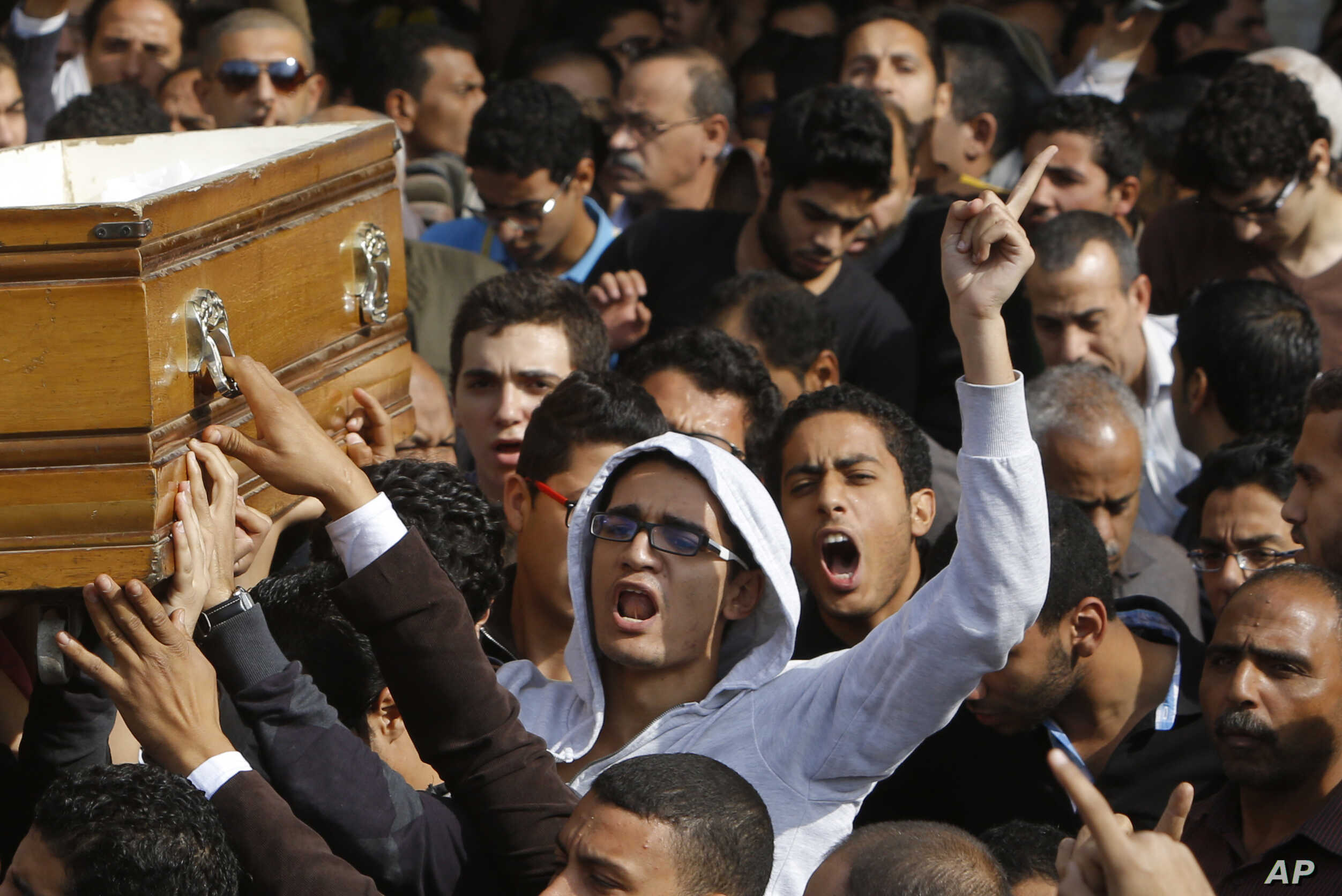 Relatives and colleagues of Mohammed Reda, 19, an Egyptian student who was killed Thursday during clashes with security forces near Cairo University, chant slogans as they carry a coffin following Friday prayers in Cairo, Egypt, Friday, Nov. 29, 2013