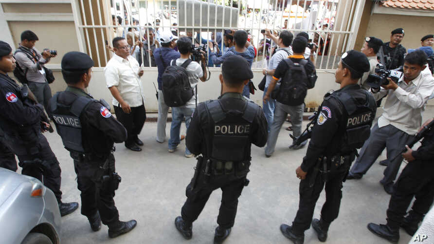 Cambodian riot police officers stand guard at the main gate of the Phnom Penh Municipal Court, in Phnom Penh, Cambodia, Aug. 15, 2015.