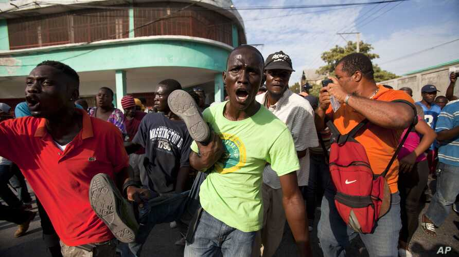 Anti-government protesters carry the body of a demonstrator who was shot to death during clashes with the National Police in Port-au-Prince, Haiti, Dec. 13, 2014.