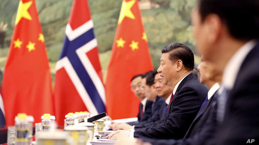FILE - Chinese President Xi Jinping speaks to Norwegian Prime Minister Erna Solberg at the Great Hall of People in Beijing, China, April 10, 2017. In another sign that their relationship was thawing, the two countries have resumed talks on a bilatera