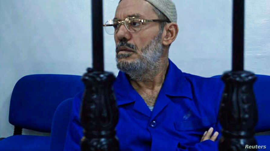Ahmed Ibrahim, former minister in the government of Moammar Gadhafi, sits behind bars during a hearing in Misrata, July 31, 2013.