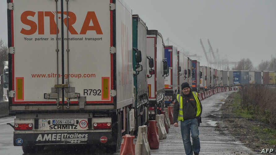 A driver walks next to trucks stuck in a traffic jam due a strike by customs agents, a few kilometers from the entrance to the Channel tunnel, in Loon-Plage, near Dunkirk, northern France, March 6, 2019.