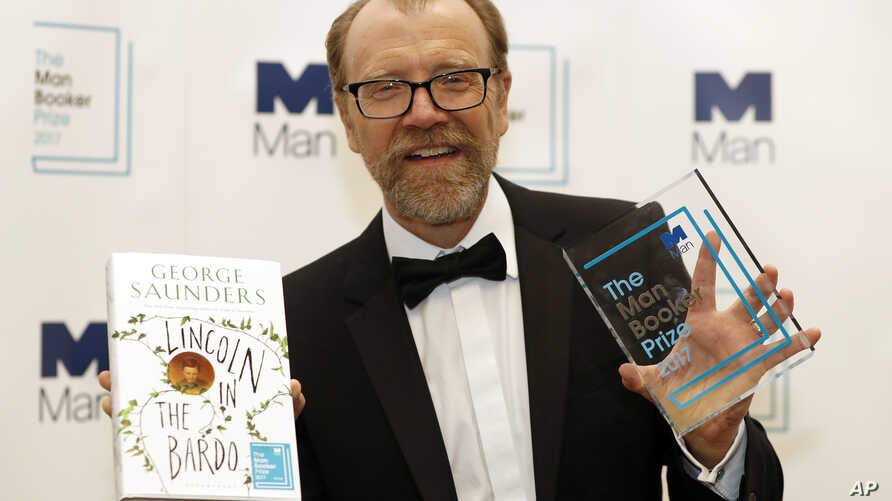 """Author George Saunders of the United States holds his book """"Lincoln in the Bardo"""" and his award as winner of the 2017 Man Booker Prize, in London, Oct. 17, 2017."""