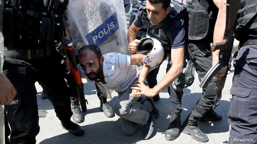 Riot police detain a demonstrator during a protest against the suspension of teachers from classrooms over alleged links with Kurdish militants, in the southeastern city of Diyarbakir, Turkey, Sept. 9, 2016.