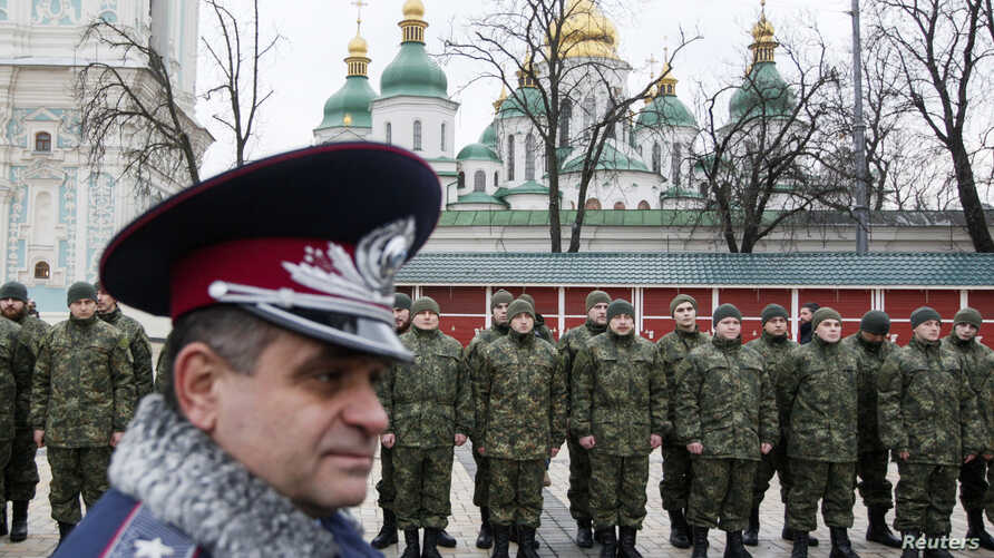 """Members of the newly created Ukrainian interior ministry battalion """"Saint Maria"""" take part in a ceremony before heading to military training, in front of St. Sophia Cathedral, in Kiev, February 3, 2015. Members of the battalion will be sent to the fr"""