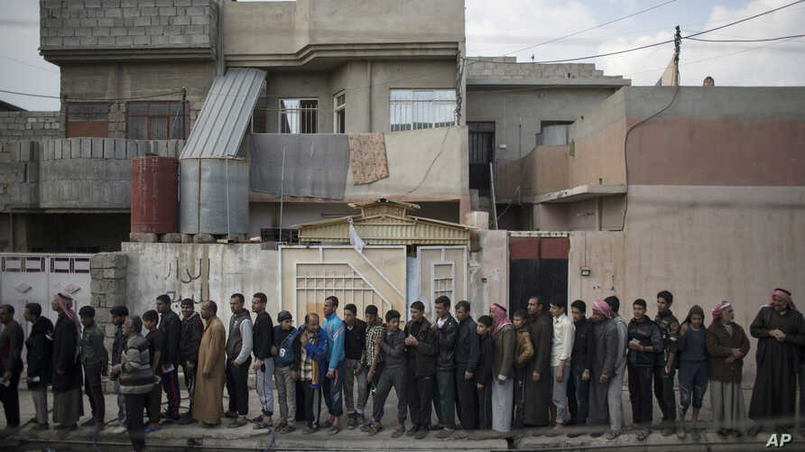 Iraqi civilians line up to receive food supplies in a neighborhood recently liberated by Iraqi security forces in western Mosul, Iraq, March 14, 2017.
