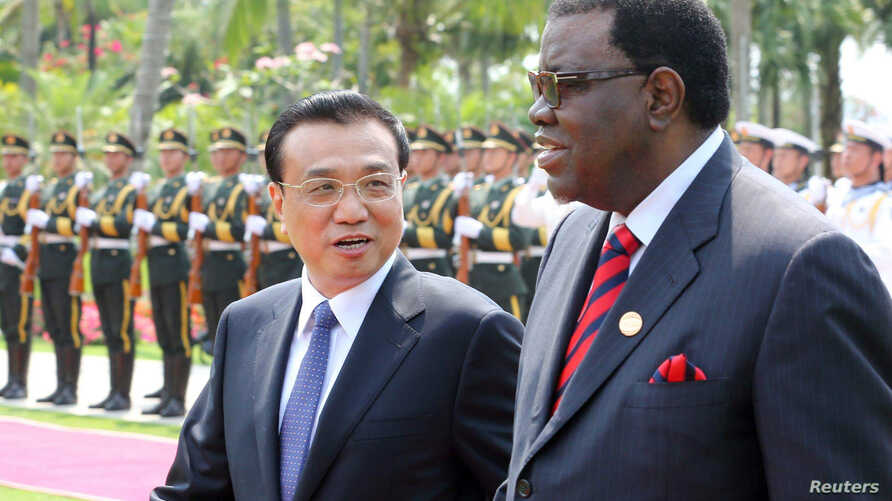 FILE - China's Premier Li Keqiang, left, talks to Namibia's Prime Minister Hage Geingob as they inspect an honor guard during a welcoming ceremony in Sanya, Hainan province, April 9, 2014.