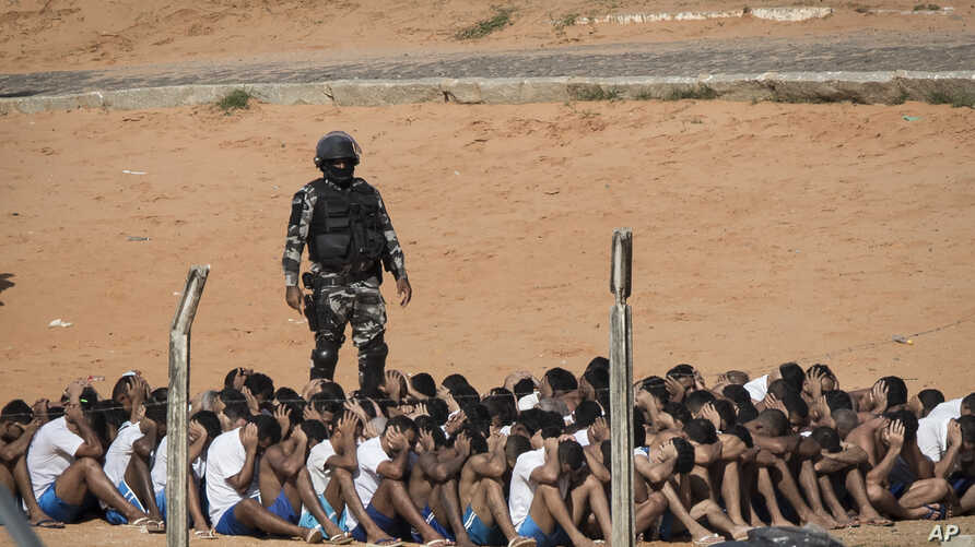 A military police officer stands next to inmates during a head count in the Alcacuz prison in Nisia Floresta, near Natal, Brazil, Jan. 24, 2017.