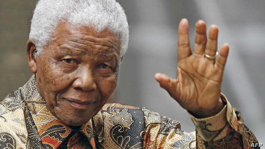 FILE - Former South African President Nelson Mandela waves to the media as he arrives outside 10 Downing Street, in central London, 28 August 2007.