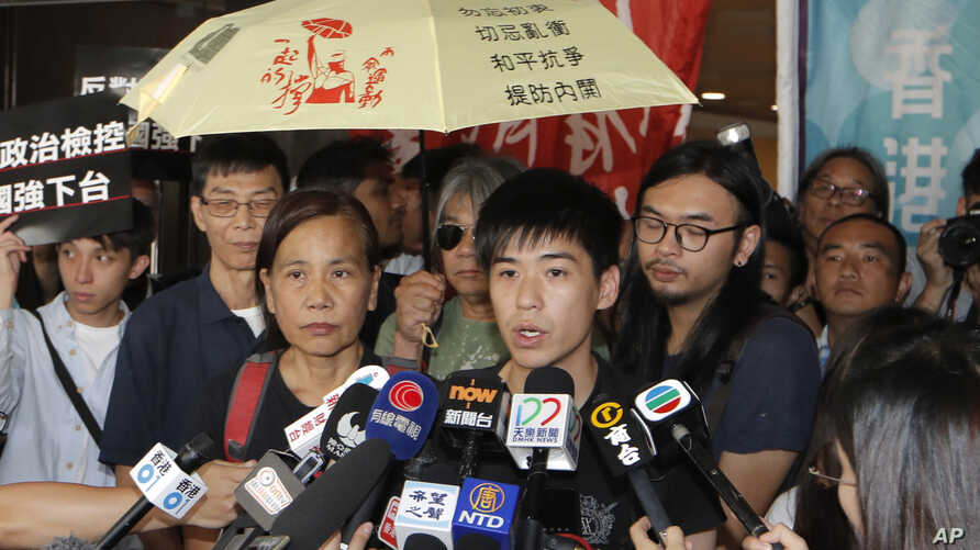 Former student leader Lester Shum, center,  one of the activists found guilty of contempt of court, speaks to media at the High Court in Hong Kong, Friday, Oct. 13, 2017.
