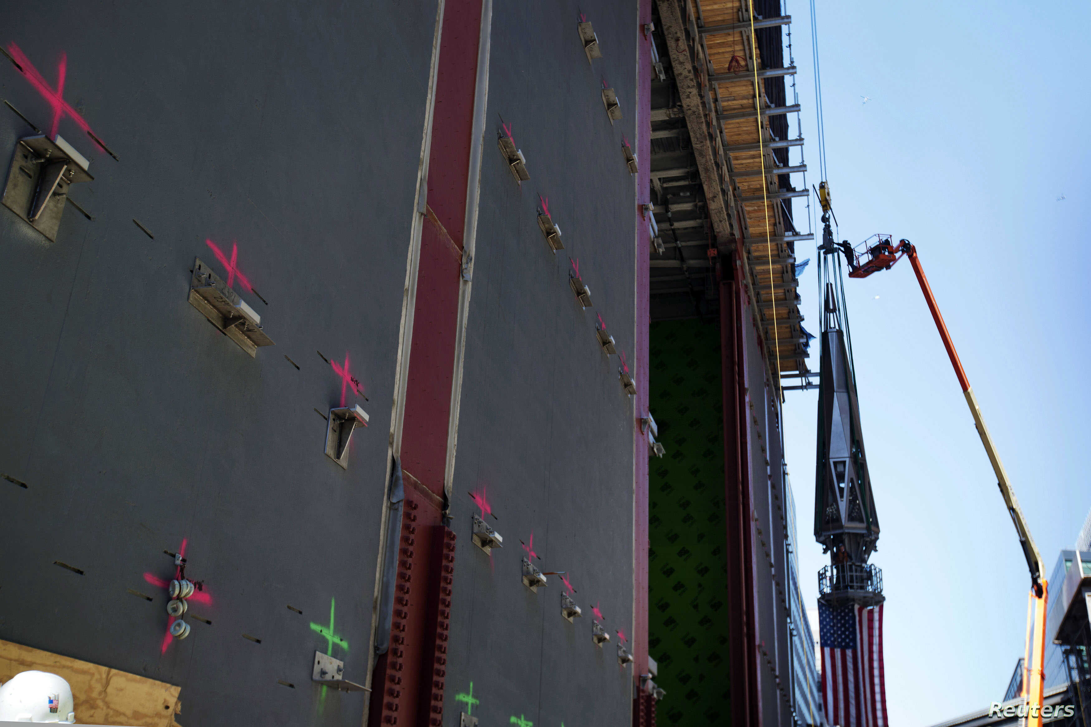 A Ground Zero worker adjusts a strap before the final piece of One World Trade Center's spire is lifted to the top of the building in New York, May 2, 2013.
