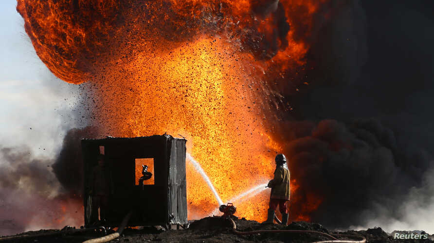 Firefighters and engineers battle fires at oil wells set ablaze by Islamic State militants before fleeing the oil-producing region of Qayyara, Iraq, Jan. 18, 2017.