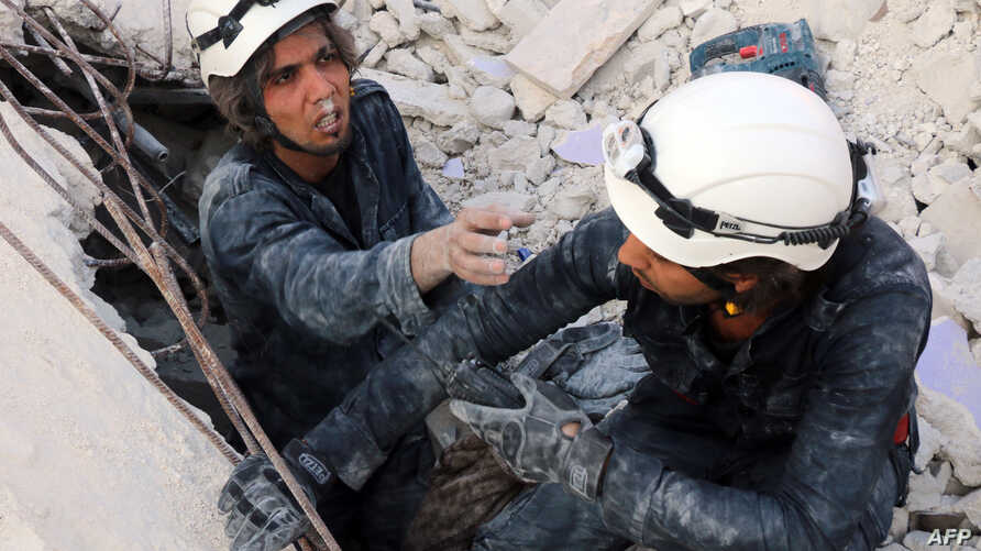 FILE - Medics search for survivors under the rubble following a reported air strike on the rebel-held neighborhood of al-Kalasa in the northern Syrian city of Aleppo, Oct. 30, 2015.