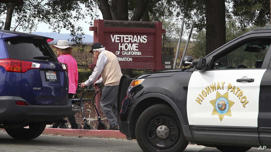 People walk to the information center at the Veterans Home of California in Yountville, Calif., March 9, 2018. A gunman took at least three people hostage at the largest veterans home in the United States on Friday, leading to a lockdown of the spraw