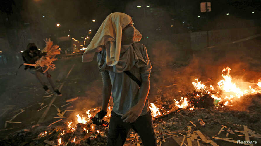 Opposition supporters walk past a burning barricade at Altamira square in Caracas, Feb. 20, 2014.
