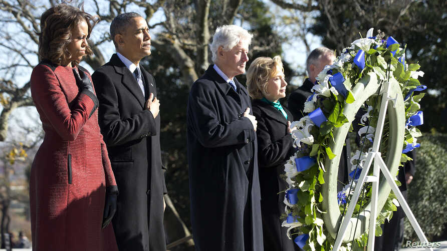 President Barack Obama (2nd L), first lady Michelle Obama (L), former President Bill Clinton (3rd L) and Hillary Clinton participate in a wreath laying in honor of assassinated U.S. President John F. Kennedy at Arlington National Cemetery, near Washi...