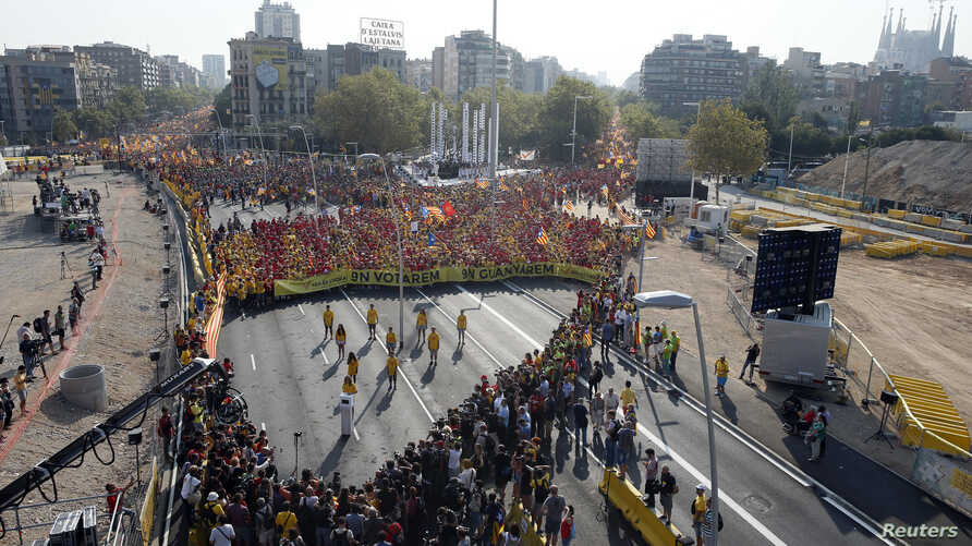 """People form a """"V"""" for """"vote"""" in red and yellow, colors of the Catalan flag, to mark """"Diada,"""" central Barcelona, Sept. 11, 2014."""