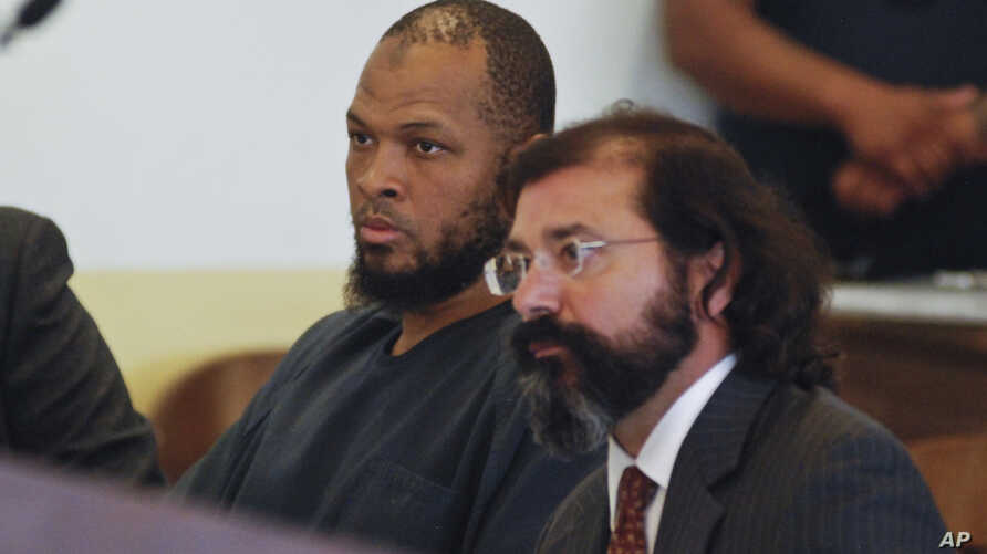 Siraj Ibn Wahhaj, left, sits next to public defense attorney Aleks Kostich at a first appearance in New Mexico state district court in Taos, N.M., Aug. 8, 2018, on accusations of child abuse and abducting his son from the boy's mother.