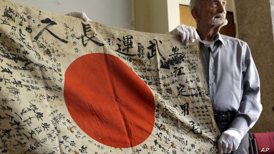 WWII veteran Marvin Strombo holds up a Japanese flag with names written on it in Portland, Ore., Monday, Aug. 7, 2017.