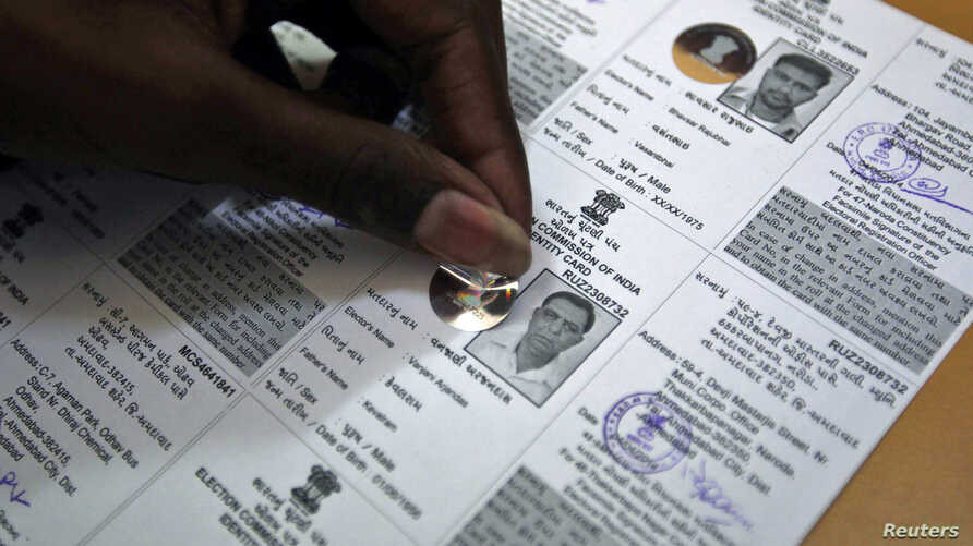 An election staff member pastes a hologram on a voter identification card at an election branch of a district administrative office in the western Indian city of Ahmedabad, April 4, 2014.