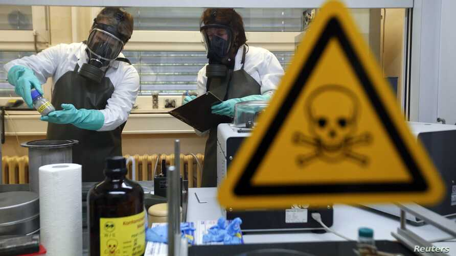 Employees of an OPCW-linked lab inspect dummy samples contaminated with a substance similar to Sarin during demonstration, Munster, Oct. 15, 2013.