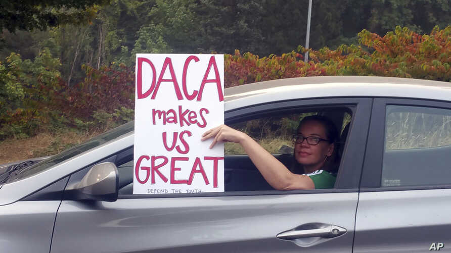 An unidentified woman holds a sign as she drives through rush hour traffic in Portland, Ore., Sept. 5, 2017.  President Donald Trump  Tuesday began dismantling the Deferred Action for Childhood Arrivals, or DACA, program, the government program prote...