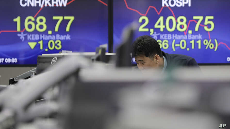 A man watches computer monitors near the screens showing the Korea Composite Stock Price Index (KOSPI), right, and the foreign exchange rate at the foreign exchange dealing room in Seoul, South Korea.