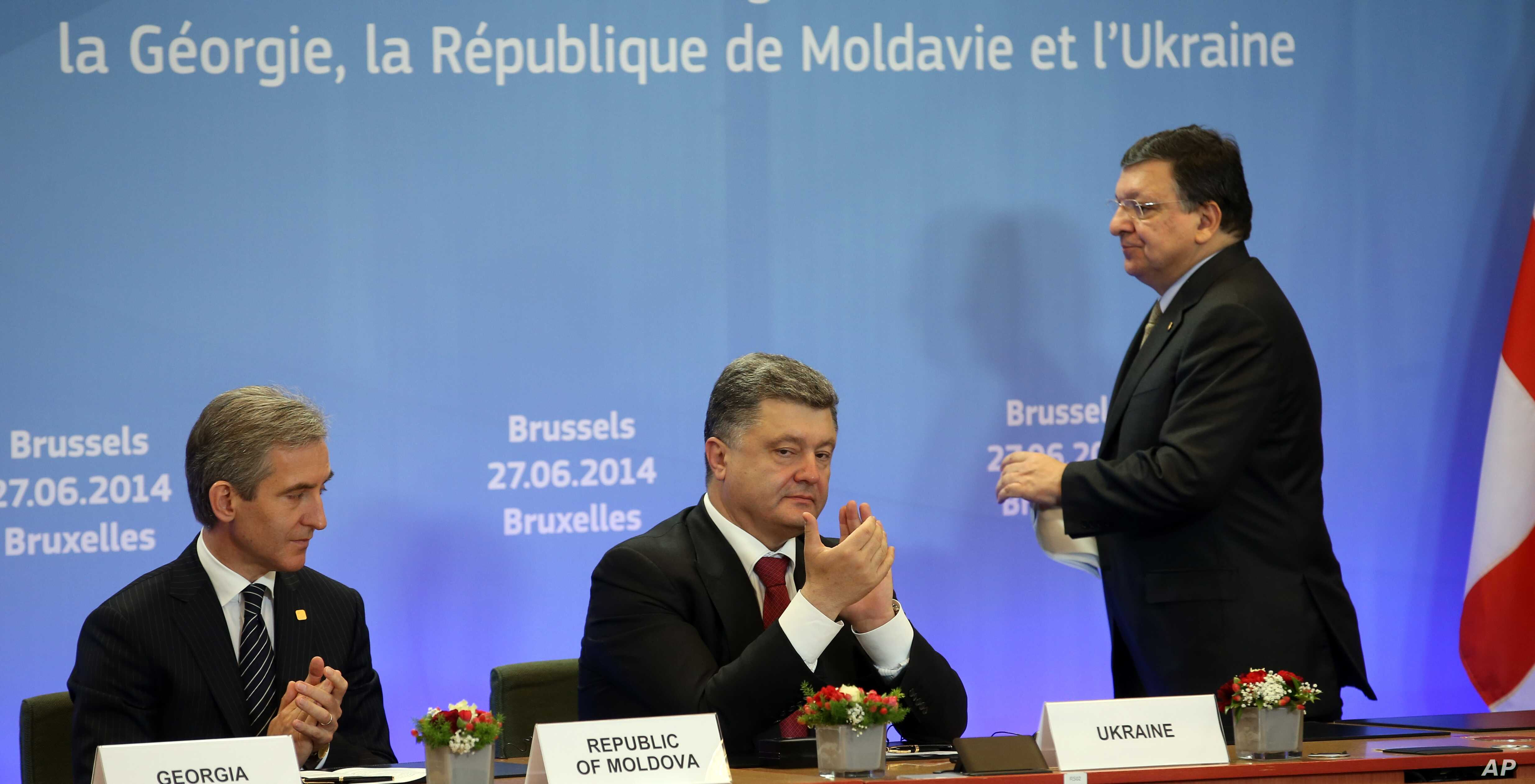 From left, Moldova's Prime Minister Lurie Leanca, Ukrainian President Petro Poroshenko and European Commission President Jose Manuel Barroso participate in a signing ceremony at an EU summit in Brussels on Friday, June 27, 2014.