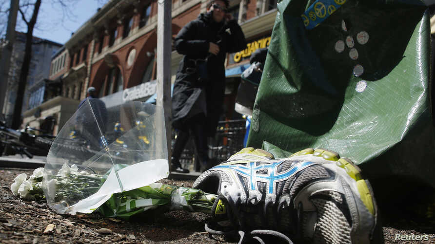A running shoe with flowers lies near the site of the second bomb blast in the 2013 Boston Marathon bombings in Boston, Massachusetts, April 16, 2014.