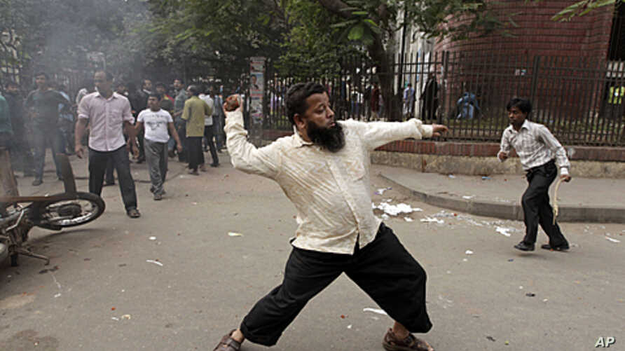 A demonstrator throws a brick at police during clashes between police and Bangladesh Nationalist Party (BNP) protesters in front of the Dhaka Judge Court in Dhaka, December 4, 2011.
