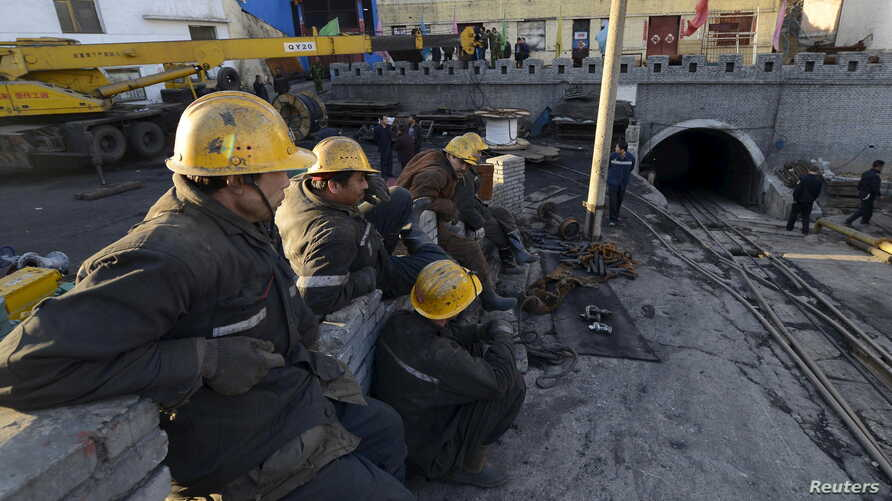 Rescuers sit next to the entrance of a coal mine after a flooding incident in Datong, Shanxi province, China, April 20, 2015.