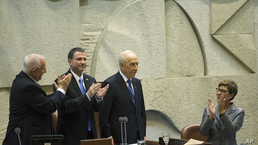 From left: Newly sworn-in Israeli President Reuven Rivlin and Parliament Speaker Yuli Edelstein applaud outgoing President Shimon Peres during a ceremony at the Knesset, in Jerusalem, July 24, 2014.